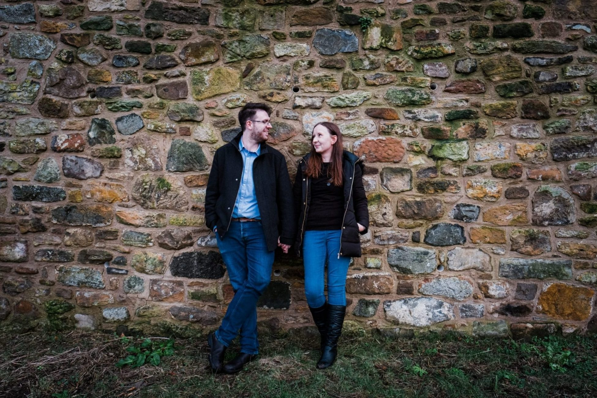An engagement portrait of a couple against a wall