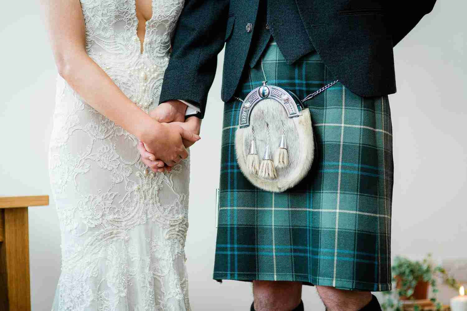 Scottish couple at a wedding ceremony holding hands