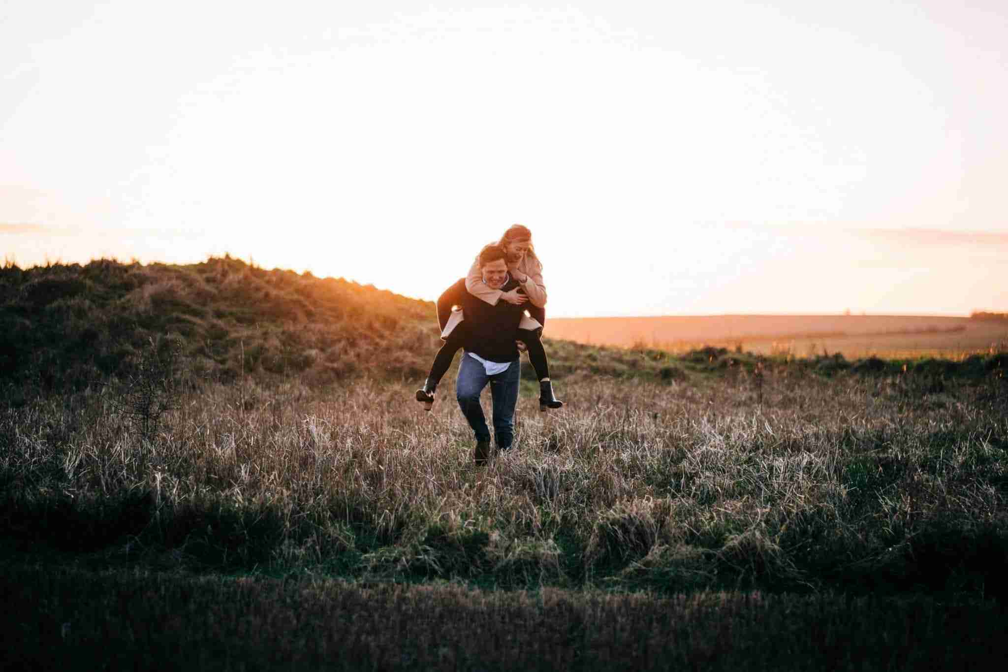 An engagement portrait of a couple at sunset