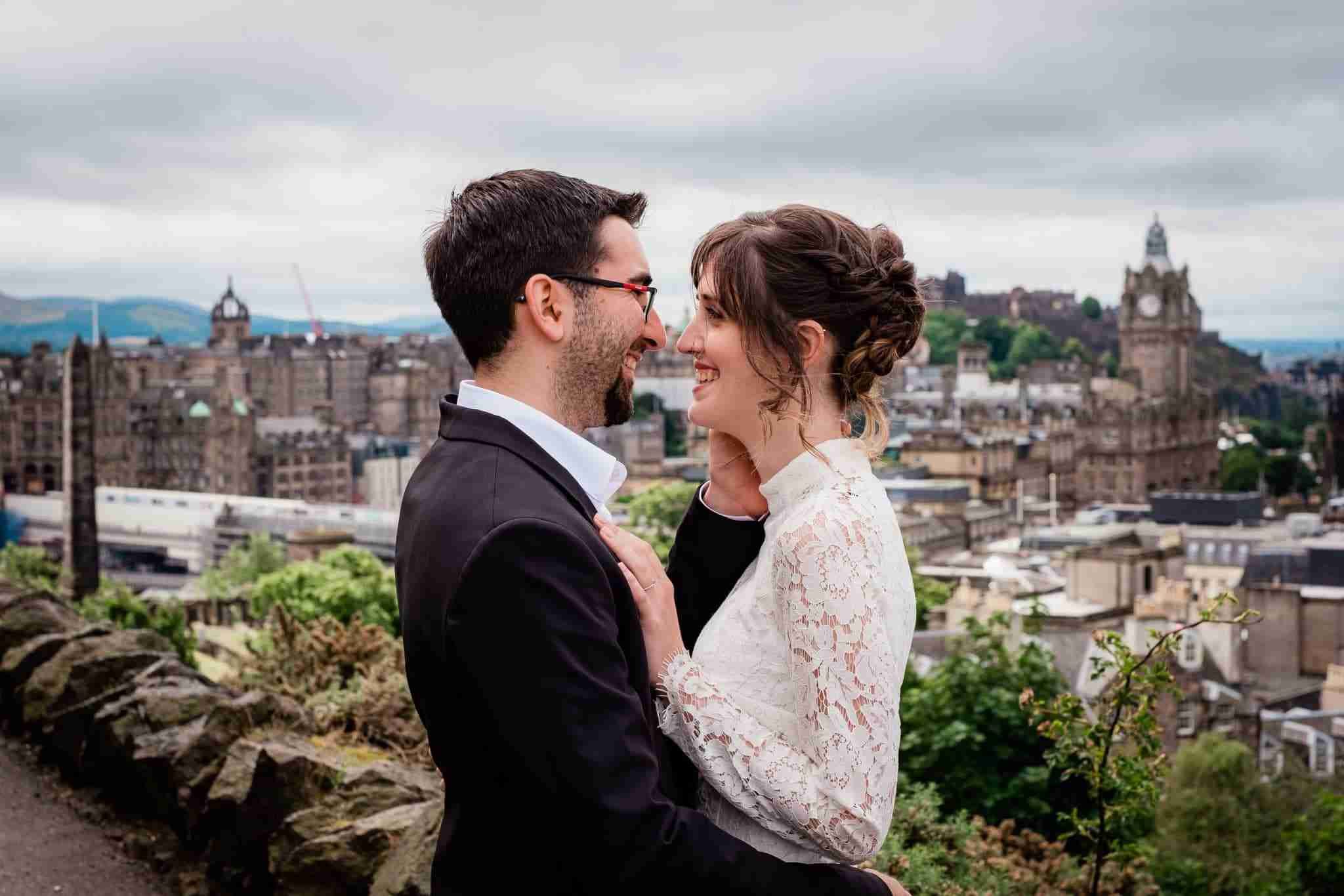 Wedding couple portrait on top of Calton Hill with Edinburgh skyline in the background