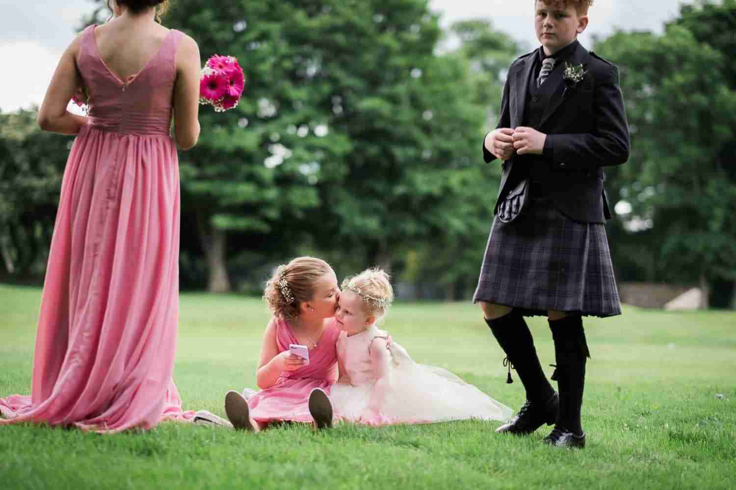 Two young bridesmaids hugging on the grass