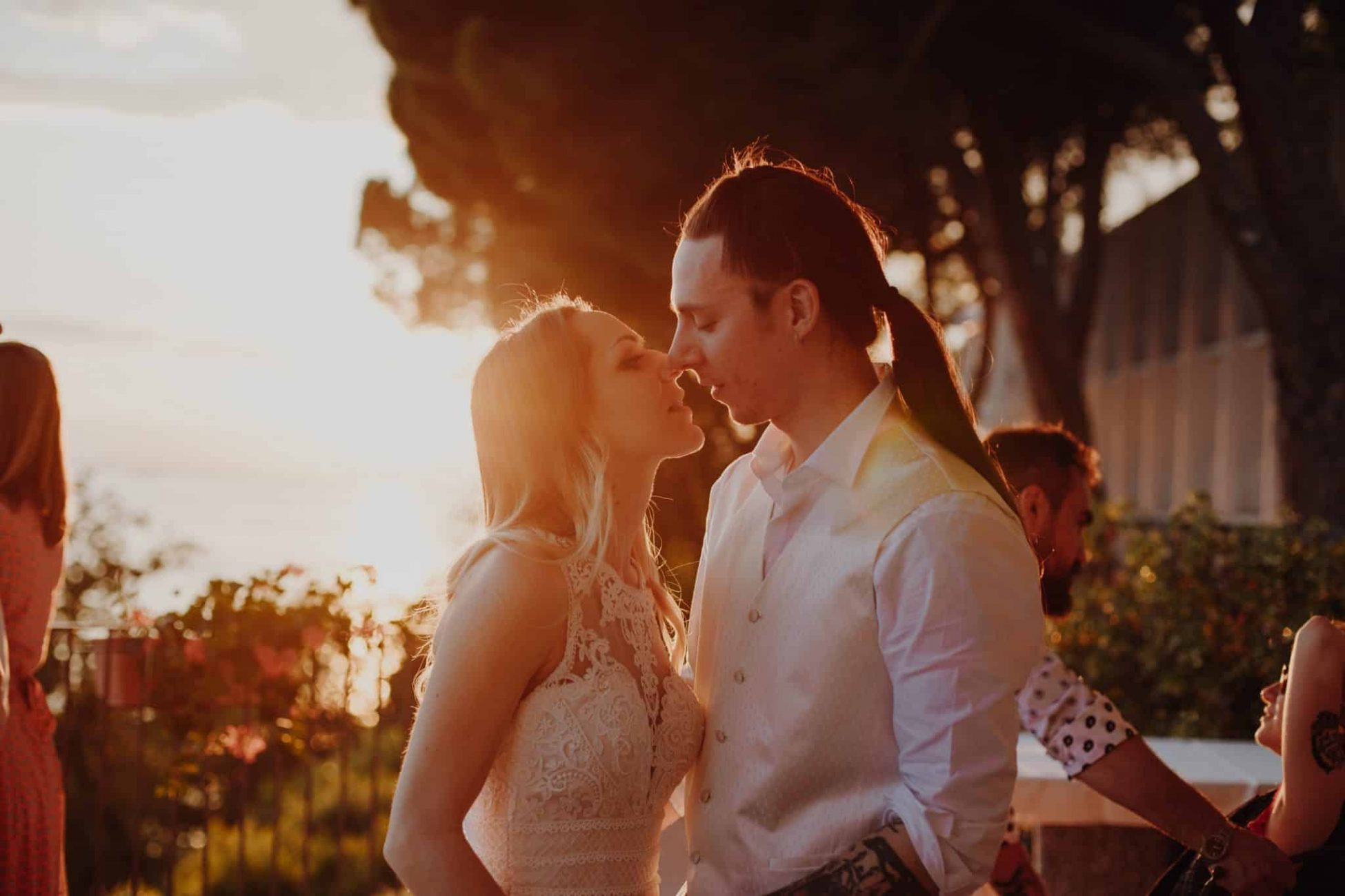 wedding portrait of couple getting close for a kiss backlit by the sun setting