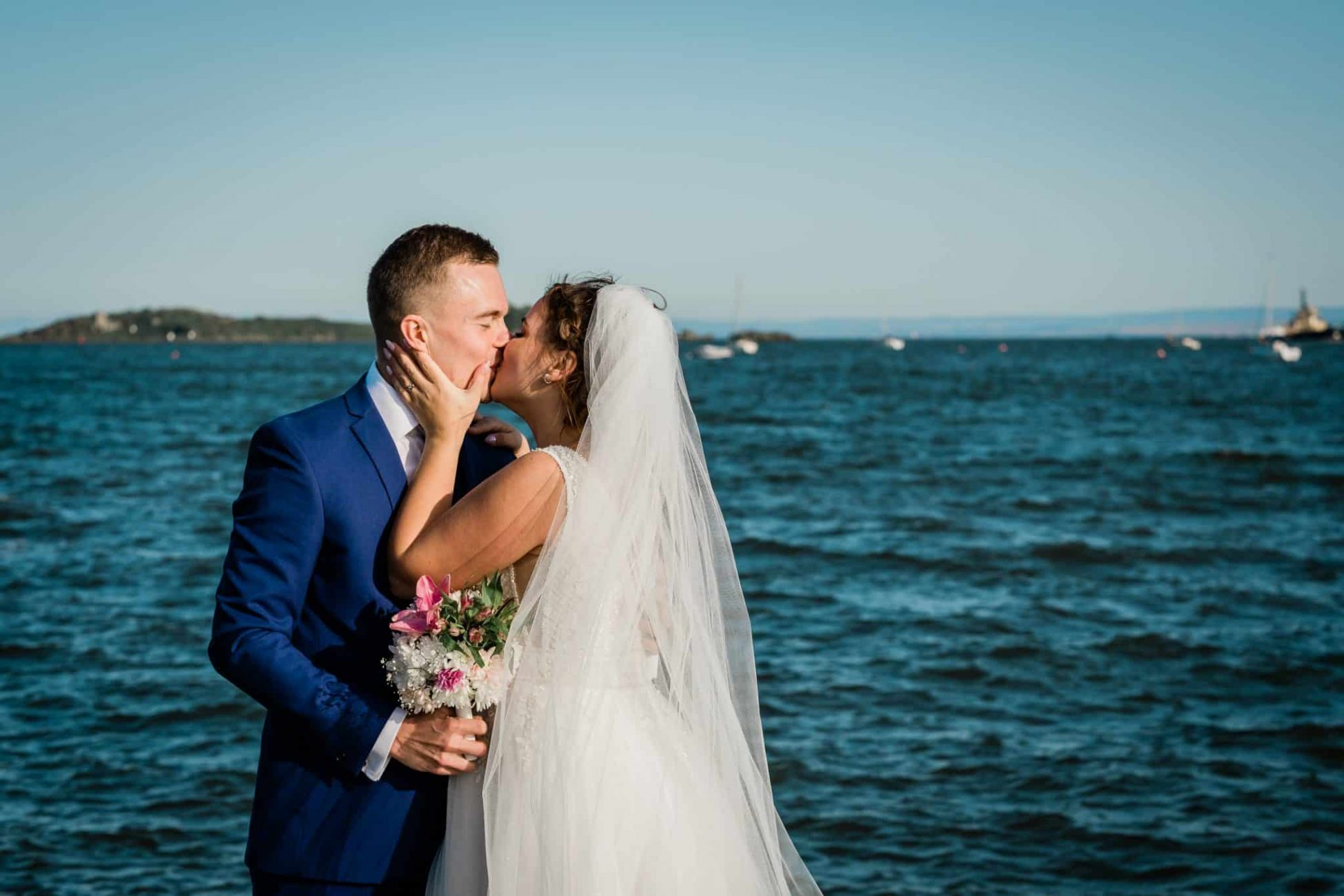 Couple kissing at their wedding with the Firth of the Forth in the background