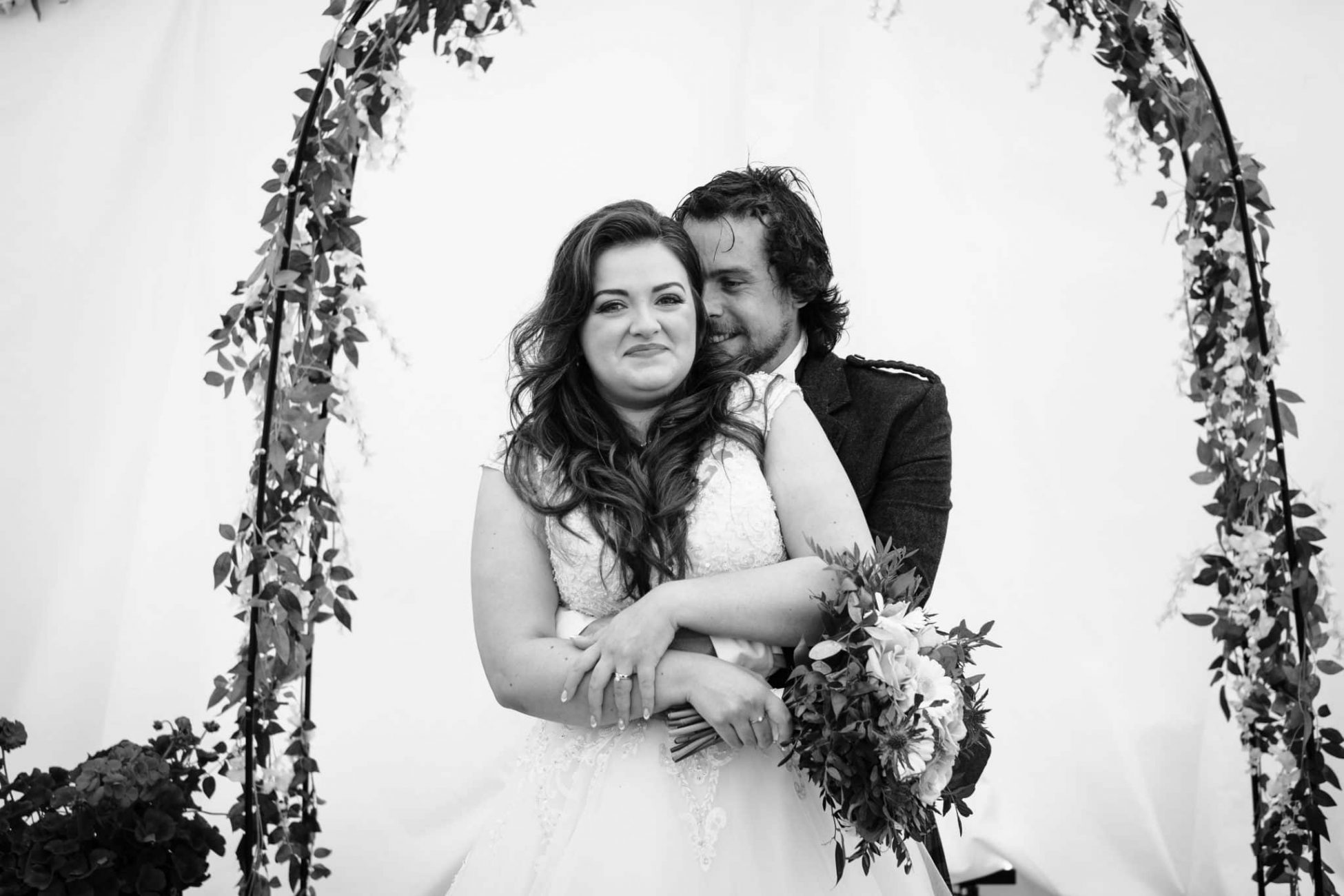 Black and white wedding portrait of couple hugging in front of a flower arch