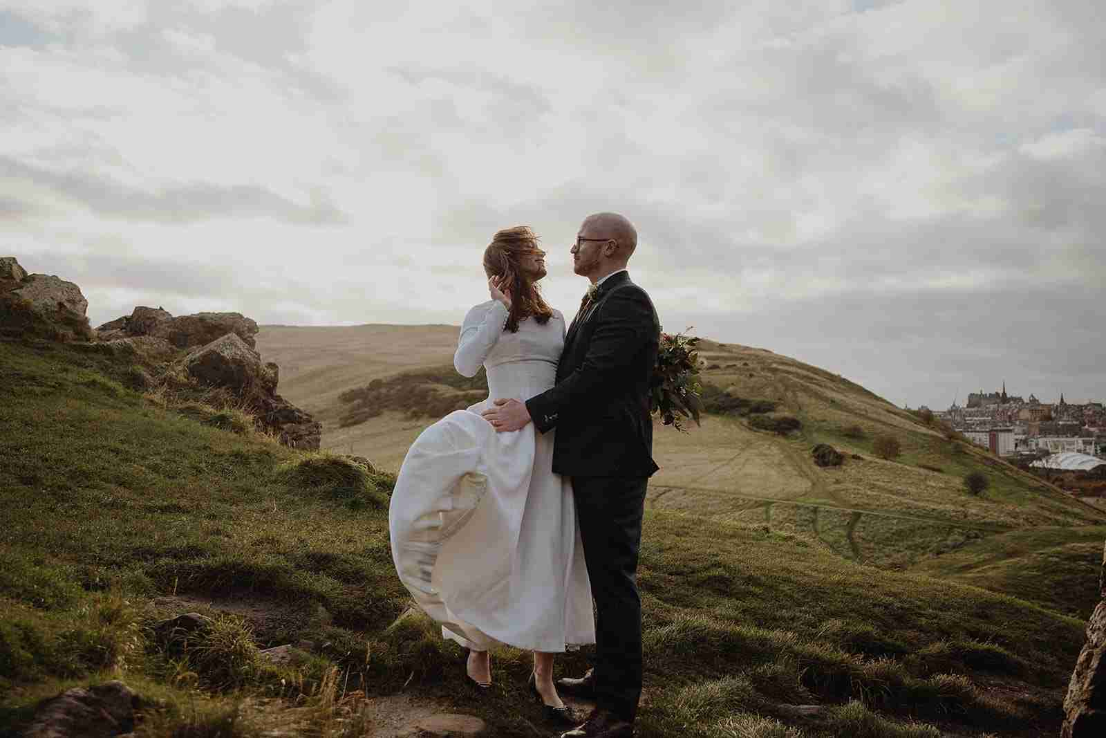 Portrait of a couple eloping in Holyrood Park during a windy day