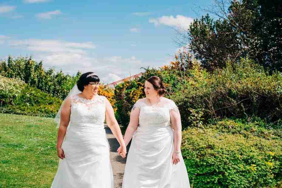 Two brides walk while holding hands
